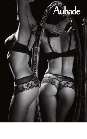 Femme portant un ensemble de lingerie de la collection Aubade à l'Amour noir face à un mirroir