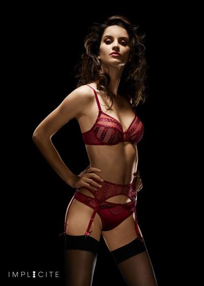 mannequin sur fond noir habillée de lingerie sexy rouge implicite