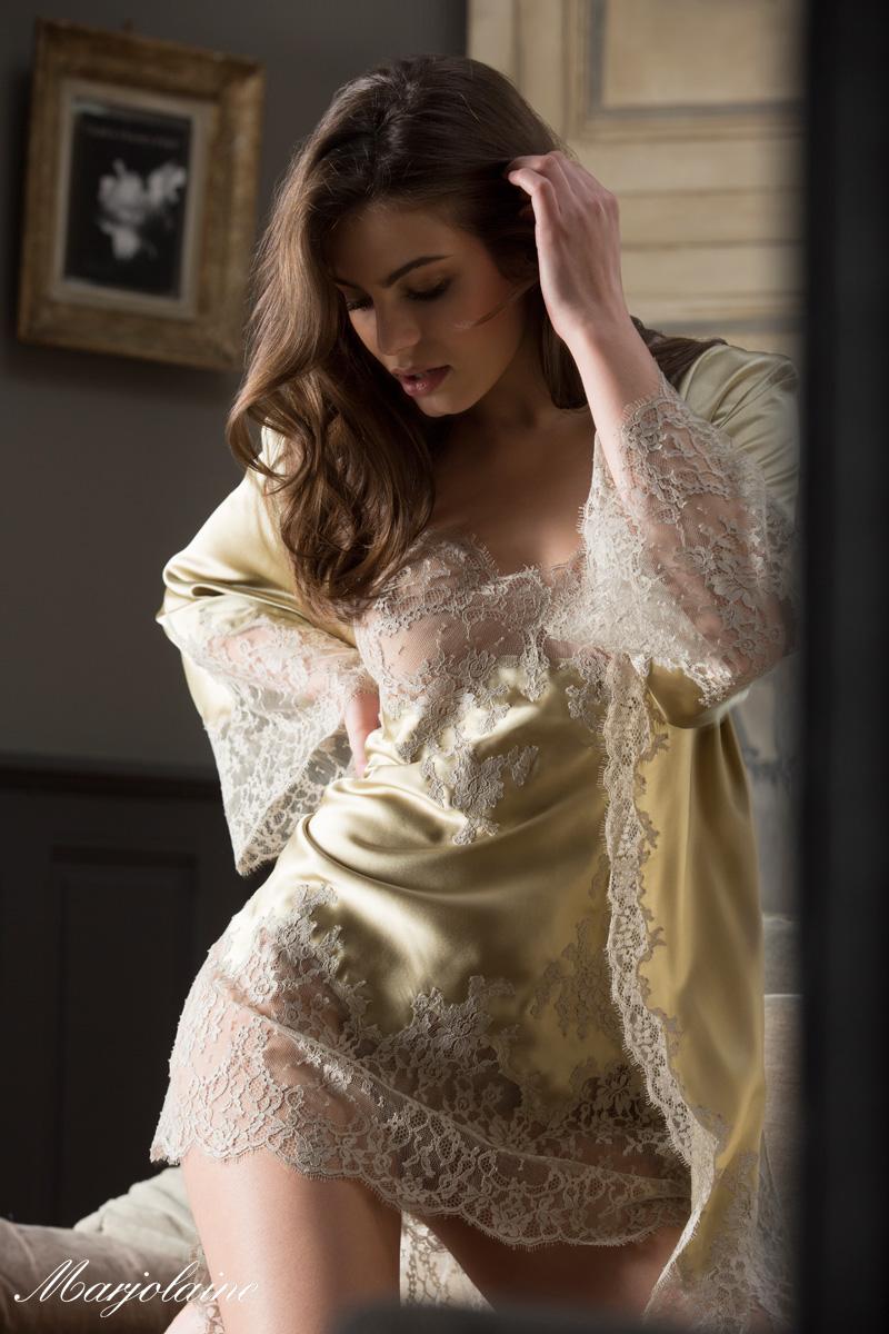 femme à genou sur un lit habillée d'un déshabillé en soie Marjolaine jaune sauge