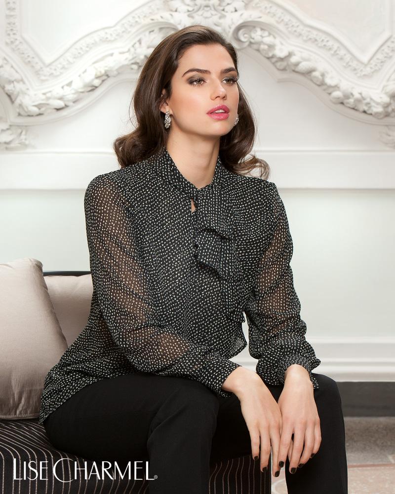 60e1053ee22 femme mannequin brune assise sur un canapé devant un fond de moulures  blanches porte une blouse