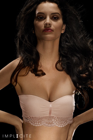 femme mannequin brune implicite porte soutien-gorge bandeau rose pâle avec des volants en dentelle sur fond noir