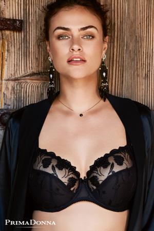 femme brune mannequin grande taille myla dalbesio porte un soutien gorge emboitant noir de la collection eternal black de prima donna avec une veste de tailleur noir devant un fond en bois
