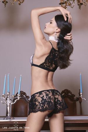mannequin de dos met ses mains dans ses cheveux porte un shorty et un soutien-gorge en dentelle noire de la marque les jupons de tess devant une table avec chandeliers de luxe