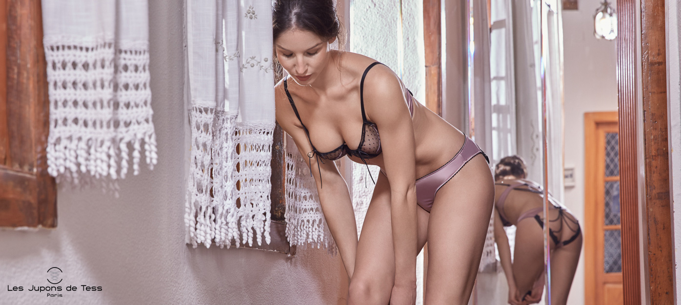 femme mannequin qui se penche en avant et porte un ensemble de lingerie coquine les jupons de tess face à un miroir