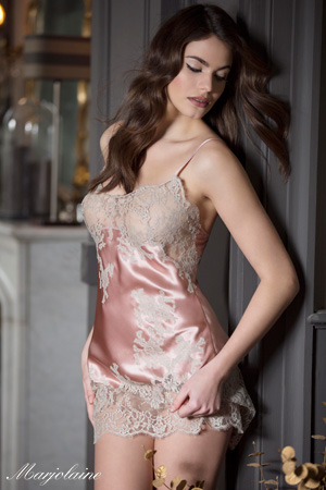 mannequin brune pour Marjolaine porte une nuisette courte ou combinette rose et blanche en soie et dentelle pose contre une porte grise