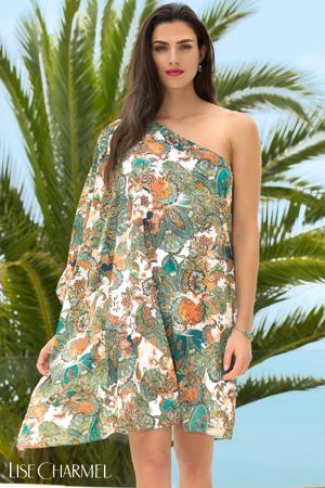 MAnnequin Lise Charmel porte un paréo asymétrique en imprimé cashmere cachemire safran devant un grand palmier