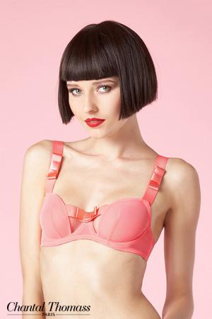 Mannequin Chantal Thomass qui porte un soutien-gorge de la collection Audacieuse en coloris pamplemousse avec armatures tulle et noeud en satin sur fond rose