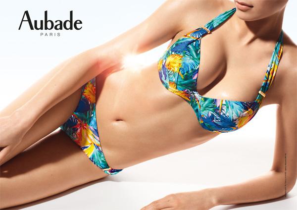 photographie aubade corps de femme mannequin allongée sur le côté, porte ensemble de maillot de bain bikini avec haut soutien-gorge push-up se noue à la nuque imprimé fleur tropicale dans les tons bleus et slip de bain brésilien