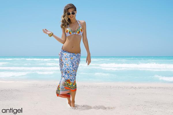 mannequin chatain porte un haut de maillot de bain triangle imprimé aux couleurs bleues rouge et jaune avec un paréo imprimé noué sur les hanches, marche devant la mer sur le sable