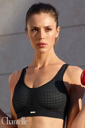mannequin en extérieur devant du béton gris porte une brassière de sport noir à petits pois blanc de la marque Chantelle