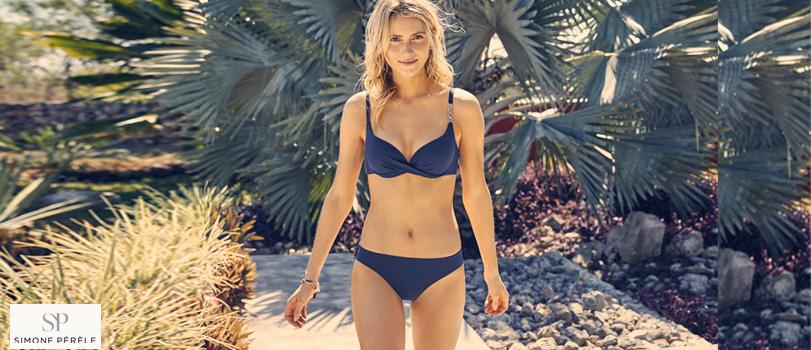 mannequin blonde porte une ensemble de maillot de bain bikini simone pérèle bleu marine, soutien-gorge push-up et slip de bain collection gold devant un chemin en pierre et des palmiers