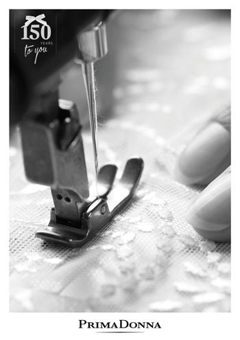 gros plan sur une machine à coudre qui brode de la dentelle de calais blanche sur de la lingerie haut de gamme de la marque Prima Donna