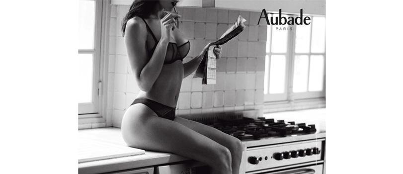 photographie aubade paris marque lingerie collection nudessence noir femme en soutien-gorge push-up et tanga assise sur un piano de cuisson cuisine