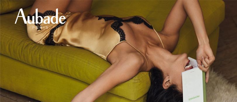 Aubade soie d'amour mannequin porte un caraco en soie et dentelle or et noir et un short lingerie allongée sur un canapé en velours vert avec un livre