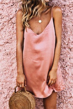 jeune femme porte nuisette rose foncé orangé en satin et porte un sac rond en osier devant un mur orangé crédit photo pinterest