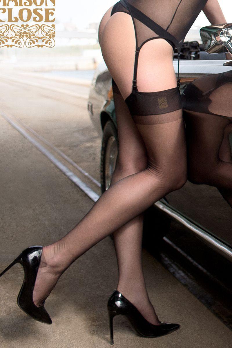 Mannequin devant une voiture portant des bas jarretière attachés à un porte jarretelles de la marque Maison Close